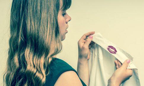 口紅が付いたシャツを見る女