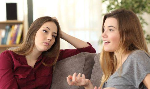 友達の話に呆れる女