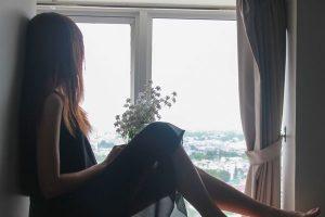 窓際に座る女