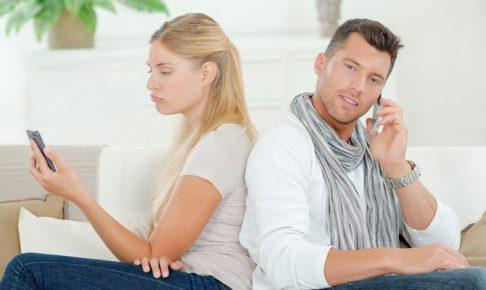 背を向けて電話するカップル
