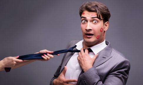 ネクタイを引っ張られる男