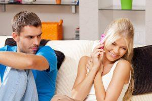 女の電話を気にする男