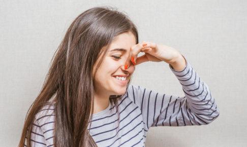 鼻をつまむ女