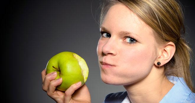 リンゴを食べている女