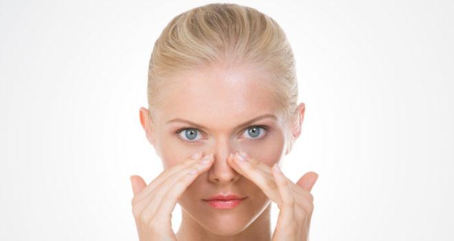 鼻をマッサージしている女性