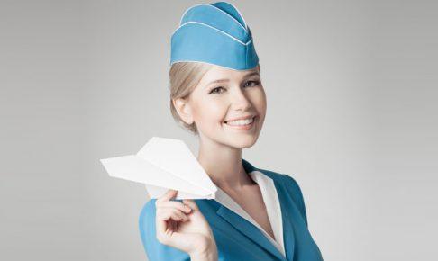 紙飛行機を持ったキャビンアテンダント