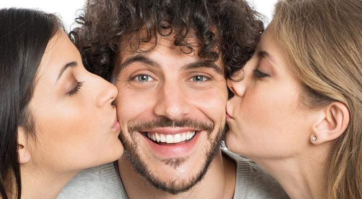 二人の女にキスされている男
