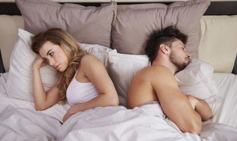 背を向けてベッドで寝ている男女