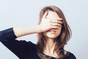 顔を隠している女