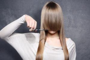 前髪を切ろうとしている女
