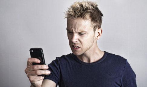 携帯を見てドン引きする男