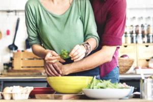 料理をしている女を抱きしめる男