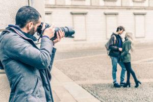 カップルの写真を撮る男