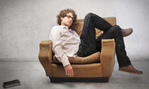 椅子にぐったり座っている男