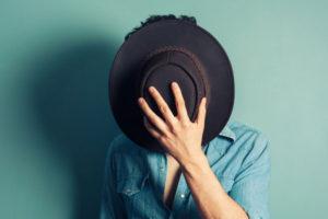 顔を隠す男