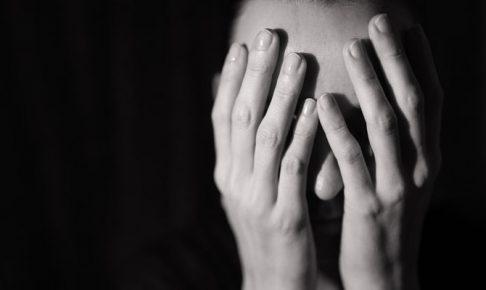 顔を手で隠す女