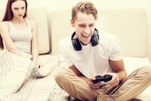 ゲームをする男と呆れる女
