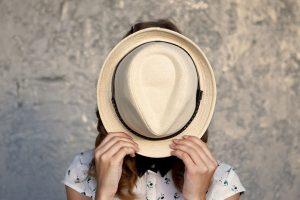 帽子で顔を隠す女
