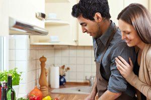料理する男を見ている女