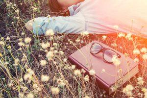 寝転がる女性と本とメガネ
