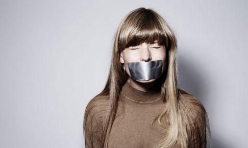 口にテープを貼られた女