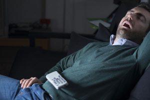 テレビを付けながら寝ている男