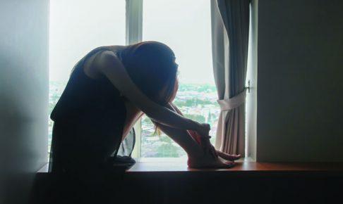 窓辺で座り込む女