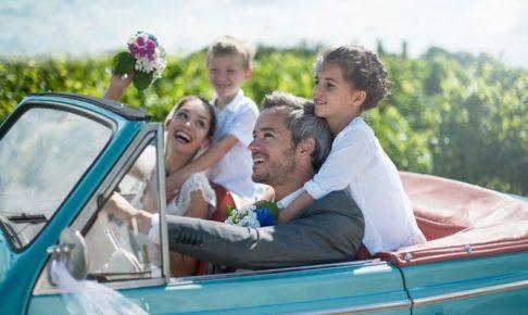 車に乗る新郎新婦と子供