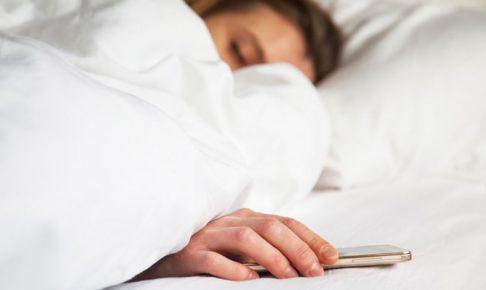 ベッドでスマホを持つ女