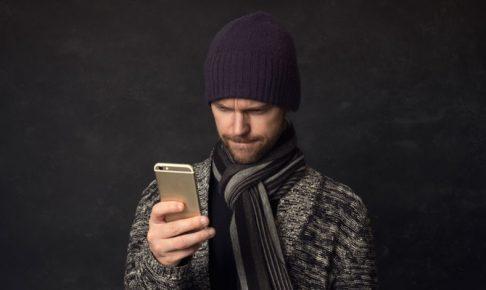 携帯を見る男