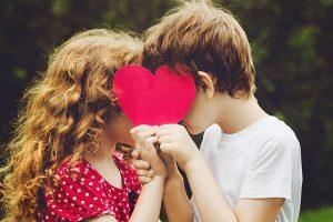 ハートで顔を隠す少年と少女