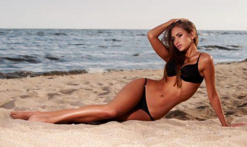 砂浜に寝そべる女