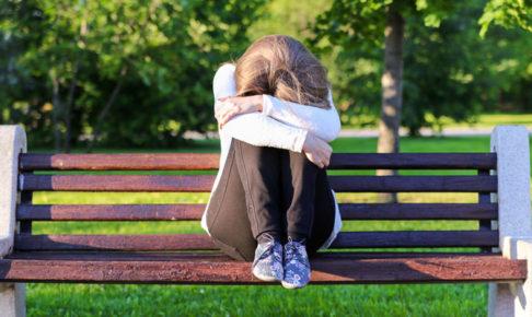 一人でベンチに座る女