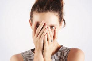 顔を隠す女