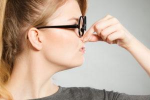 鼻を抑える女